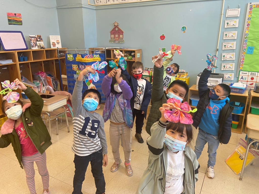 students holding multi-colored tissue paper butterflies up that they created themselves