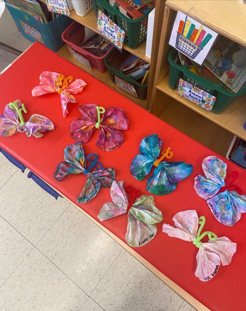 multi-colored tissue paper butterflies are laid out on a red table